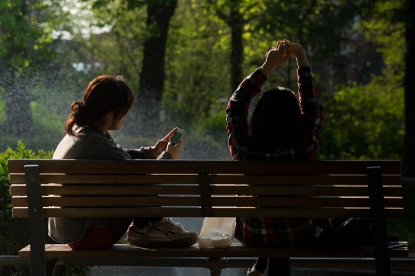 female-friends-relaxing-on-bench-in-park